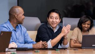Three people at boardroom table